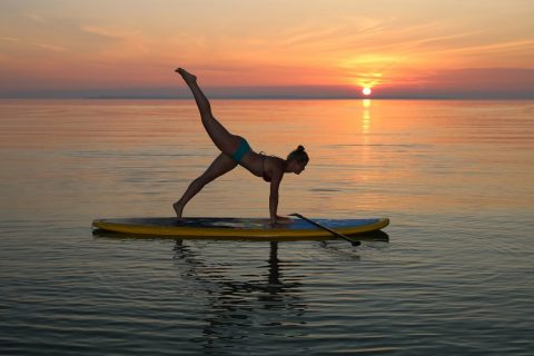 Girl is performing Yoga on Yoga Paddle Boards